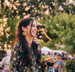 woman smiling holding glass of wine