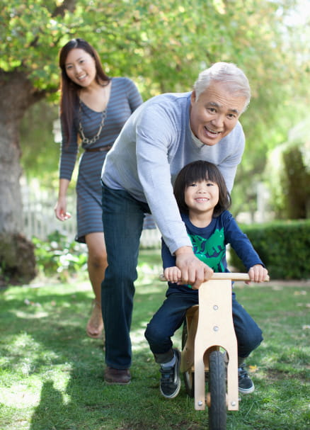 grandfather teaching child to ride bike while mother watches in the background